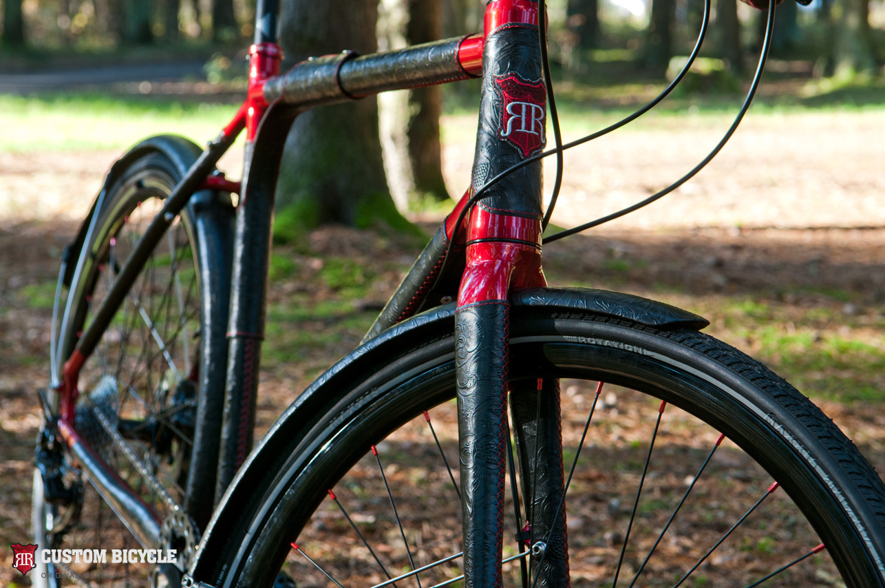 Bicycle fork covered with a natural ornamental black leather and red threads